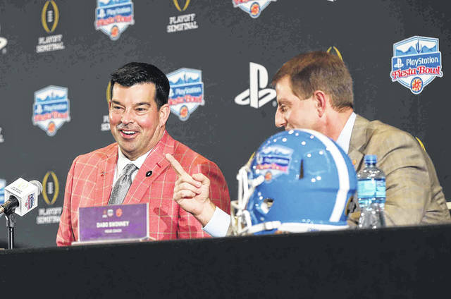 Ohio State Coach Ryan Day (left) smiles as Clemson Coach Dabo Swinney makes a point during the Playstation Fiesta Bowl press conference Friday.