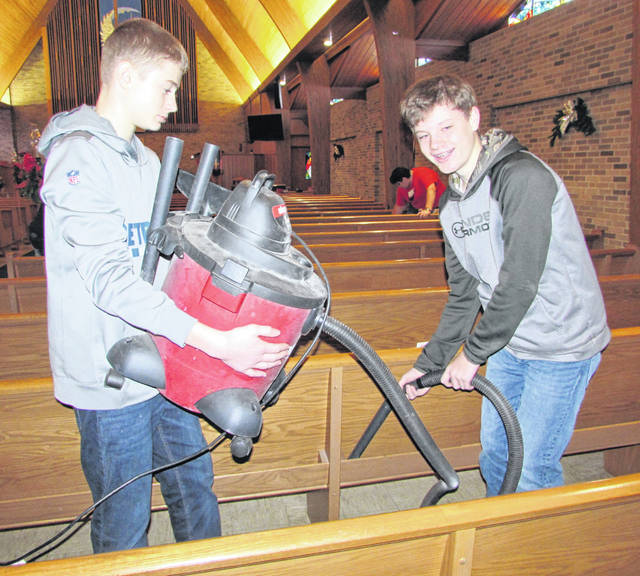 From left are Jaren Westrick and Alex Wagner, Glandorf Elementary eighth graders, vacuuming the sanctuary at Trinity United Methodist Church in Ottawa.