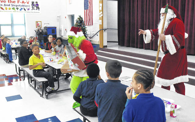 Santa Claus chases the Grinch after he steals Santa's presents at Freedom Elementary School on Friday.
