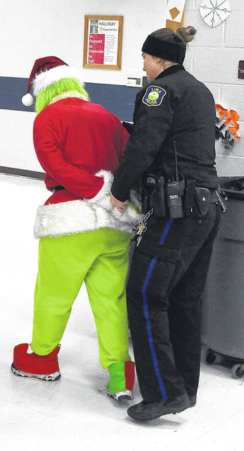 Lima Police C.O.P. officer Brittney Wyerick arrests and handcuffs the Grinch after he stole presents from Santa at Freedom Elementary School on Friday.