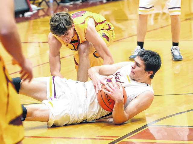 Kalida's Luke Erhart goes to the floor for a loose ball with New Bremen's Griffen Roetgerman during Monday's game at Kalida High School.