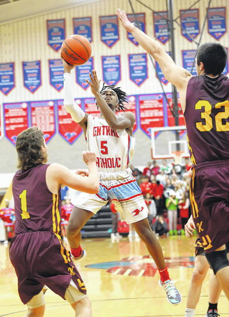 Lima Central Catholic's Biggz Johnson puts up a shot against Kalida's Ayden Warnecke (1) and Luke Erhart during Friday night's game at LCC.