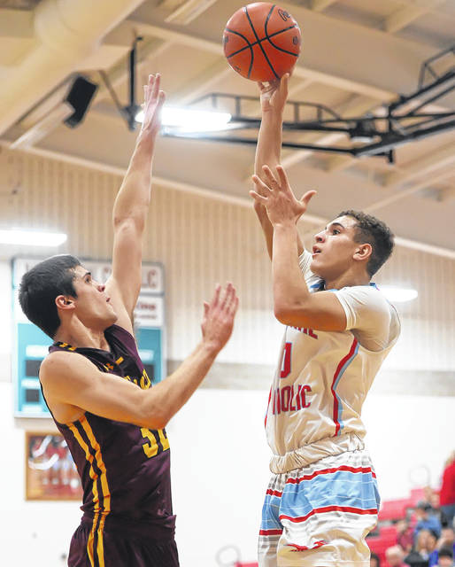 Lima Central Catholic's Rossy Moore puts up a shot against Kalida's Luke Erhart during Friday night's game at LCC.