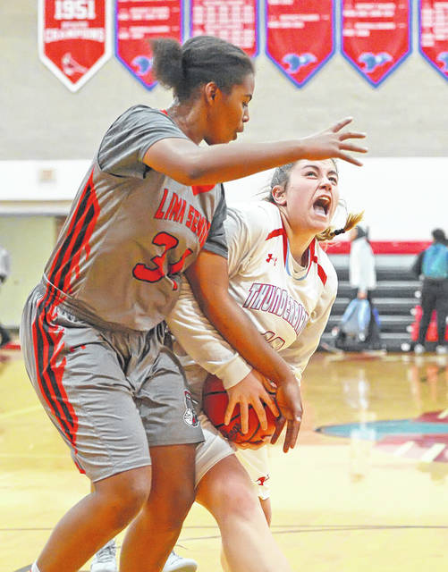 Lima Central Catholic's Rosie Williams drives to the basket against Lima Senior's Cheyanne Bean during Saturday's game at Msgr. Edward C. Herr Gymnasium.  Richard Parrish | The Lima News