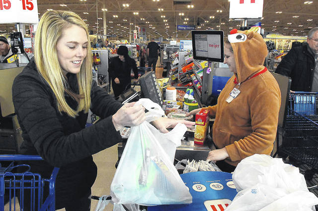 Haley Fosnaugh, right, a cashier at Meijer, wears a reindeer jacket while ringing up last-minute items for Laura Schaub, left, of Lima, on Monday morning. Six percent of Americans said in a survey they planned to shop right through today, Christmas Eve.