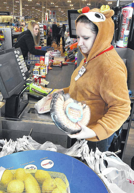 Haley Fosnaugh, right, a cashier at Meijer, wears a reindeer jacket while ringing up last-minute items on Monday morning. Gift cards, fruit baskets and board games have been popular this year, Meijer's store manager Mark Campbell said.