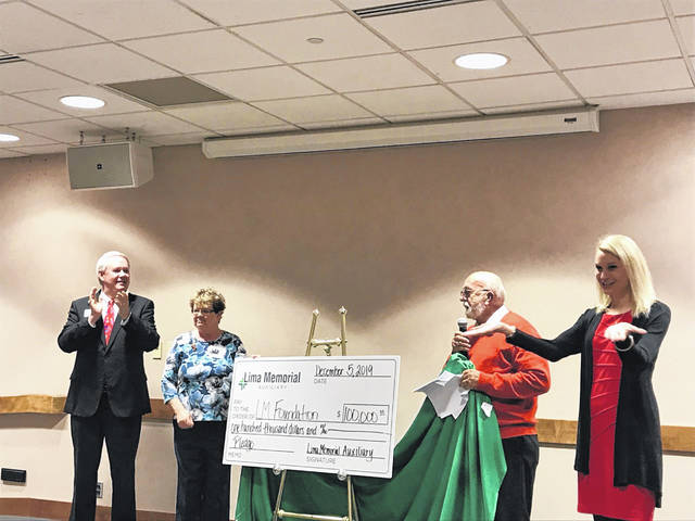 Lima Memorial Hospital Auxiliary President-elect David McCluer (second from right) presents a $100,000 check to the Lima Memorial Foundation during the auxiliary's annual meeting on Thursday. The donation will benefit the redesign of the hospital's welcome center.