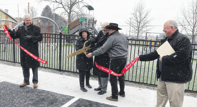 Mike Swick, of Lima Memorial Health System, left, and Ric Stolly, right, of Lima Public Works hold a ribbon while Mayor David Berger and Carol and Ray Kenny of Lima cut it during the opening of the first all-abilities playground at Lincoln Park.