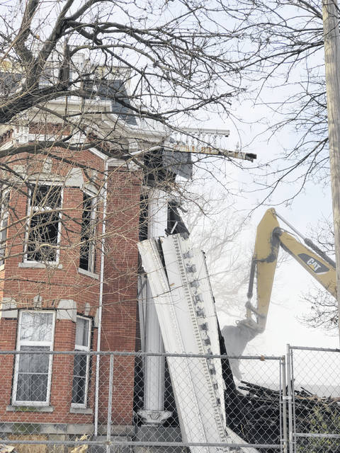 Construction crews tear off the two-story fluted Corinthian columns from the Hughes-Russell mansion, 649 W. Market St., on Friday. The former YWCA location and its attached annex are both just memories now. Senior apartments will be built along Spring Street, but there are no immediate plans for the property along Market Street.