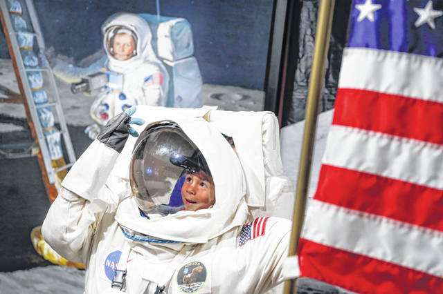In this July 20 photo, visitors pose for photos beside a portrait of Neil Armstrong at the Armstrong Air and Space Museum in Wapakoneta as special events got underway for visitors commemorating the 50th anniversary of the first moon landing. (AP Photo/John Minchillo)