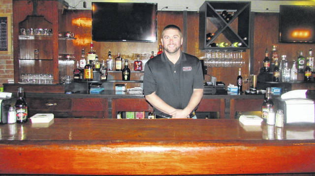 Kyle Bendele, owner of Canalside Burgers & Brew, stands in the bar area of his new business in downtown Ottoville.