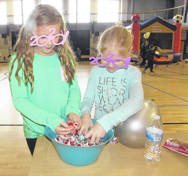 Ava Black, 9, of Ottawa, and Bridget Niese, 9, of Miller City, wear 2020 glasses to celebrate the new year and pick out candy during a party at Leipsic Community Center.