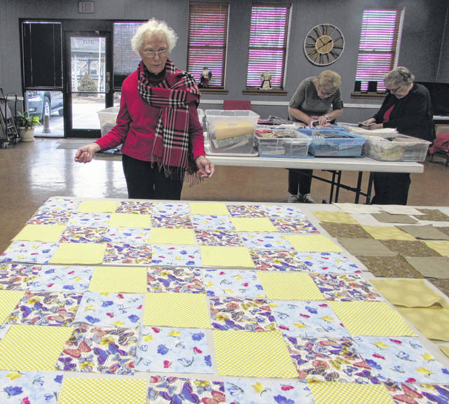 Agnes Kleman, Ottawa Senior Center Quilt Club member, lays out pieces of fabric that will be used to make a lap quilt for hospice patients at Putnam County Homecare and Hospice.