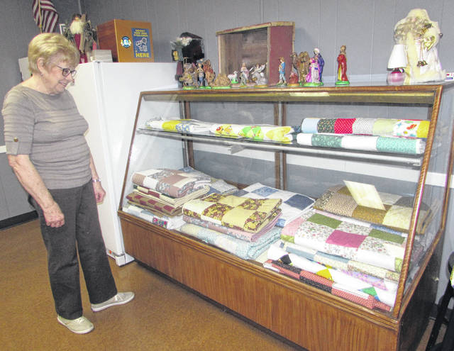 Norma Brinkman, Ottawa Senior Center Quilt Club member, looks at quilts that have been made for hospice care patients.