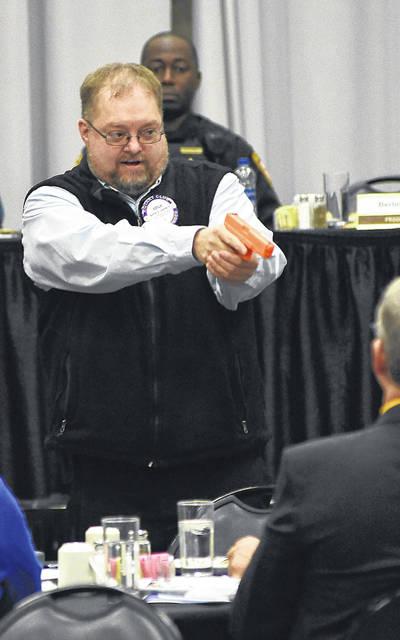 Using a training pistol, Berlin Carroll demonstrates how many lives could be taken in 2.5 seconds during a active shooter scenario demonstration at Lima Rotary luncheon on Monday.