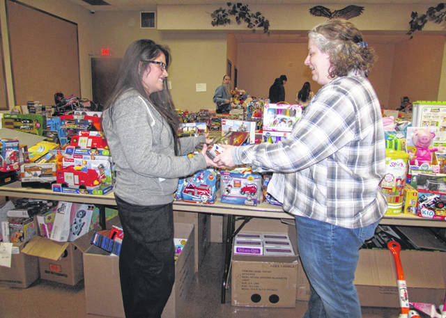 Andrea Gossard, left, picks out a toy for her son with the help of Danielle Miceli, volunteer, at Putnam County Thrift Store Toys for Tots giveaway Wednesday.