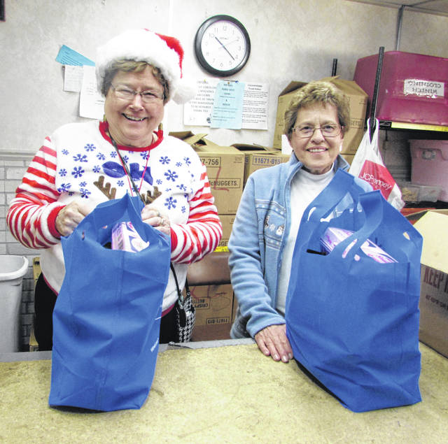 From left are Putnam County Thrift Store volunteers Bertha Hermiller and Jean Cox with bags of food that were distributed to those in need.