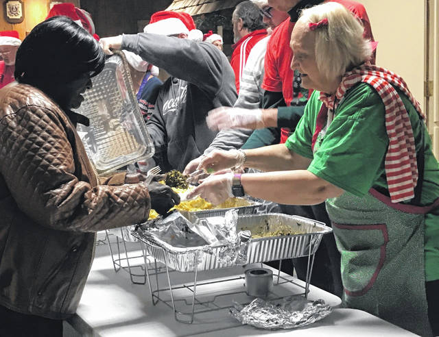 Michele Risser, right, serves collard greens to a guest at Lima's free community dinner at the VFW Post 1275 on Wednesday.