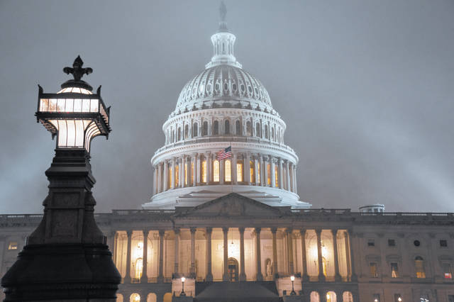 The U.S. Capitol in Washington is shrouded in mist, Friday night, Dec. 13, 2019. This coming week's virtually certain House impeachment of President Donald Trump will underscore how Democrats and Republicans have morphed into fiercely divided camps since lawmakers impeached President Bill Clinton.