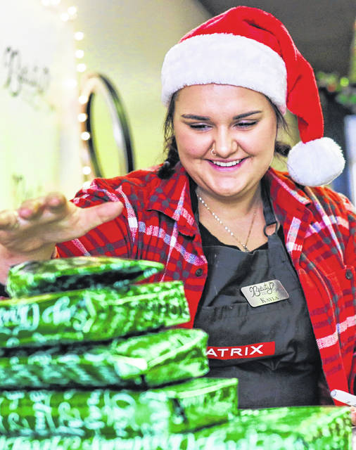 Kayla Carpenter of Lima wraps presents during the Downtown Lima Holiday Festival. Amanda Wilson |The Lima News