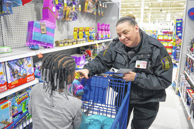 Officer Amanda Leugers smiles with her shopping buddy 6-year-old O'niyah Thomas of Lima during the FOP Cops and Kids event at Meijer on Saturday morning.