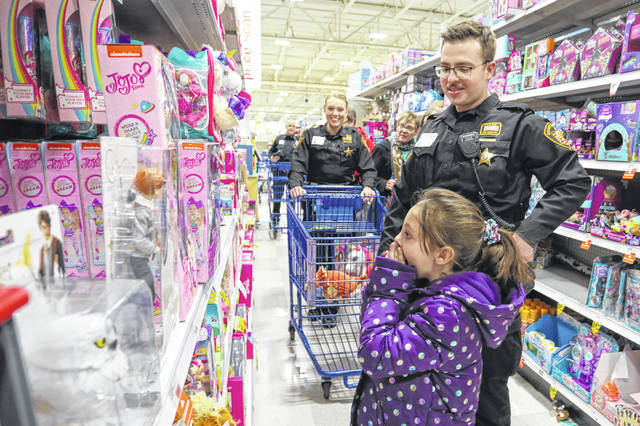 Seven-year-old Aleana Adkins, of Lima, reacts to a doll she has been wanting while she shops with deputy Konner Kranz during the FOP Cops and Kids event at Meijer on Saturday morning.