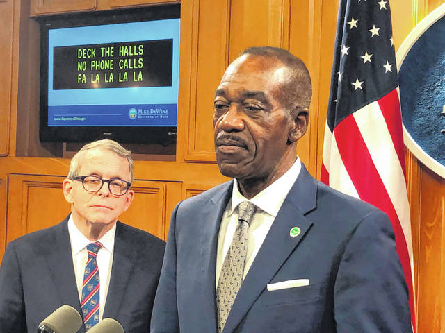 Jack Marchbanks, right, the Ohio Transportation Department director, reflects on the damage caused by distracted driving in the state, at a news conference promoting safe holiday driving and also attended by Ohio Gov. Mike DeWine, on Friday, Dec. 20, 2019, in Columbus, Ohio. DeWine said he wants distracted driving made a primary offense and promised a legislative proposal soon.