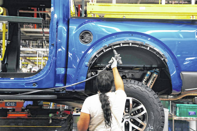 FILE - In this Sept. 27, 2018, file photo a United Auto Workers assemblyman works on a 2018 Ford F-150 truck being assembled at the Ford Rouge assembly plant, in Dearborn, Mich. Ford Motor Co. said Tuesday, Dec. 17, 2019, that it is adding 3,000 jobs at two factories in the Detroit area and investing $1.45 billion to build new pickup trucks, SUVs, and electric and autonomous vehicles. At the Dearborn truck plant $700 million will be invested.