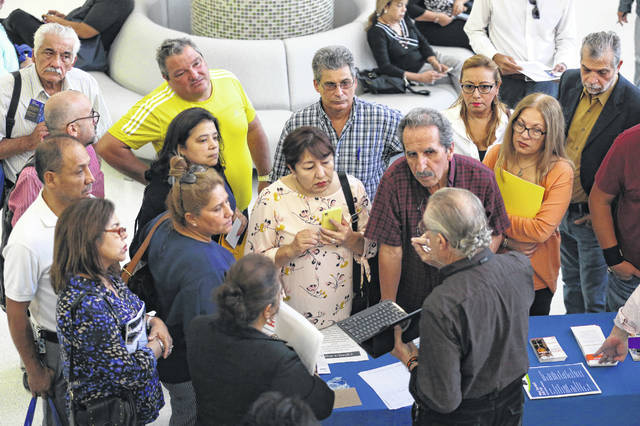FILE - In this Sept. 18, 2019, file photo people inquire about temporary positions available for the 2020 Census during a job fair designed for people fifty years or older in Miami. On Friday, Dec. 6, the U.S. government issues the November jobs report.