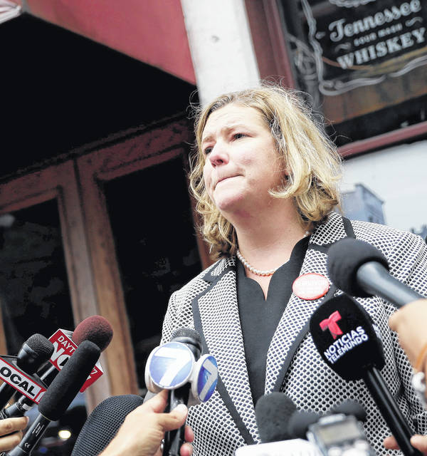 """Dayton Mayor Nan Whaley, shown speaking to the media following a mass shootin, later recalled: """"It's 6 in the morning and there are these things left, like meat on the taco truck, and the piles of shoes. There was this one car, police were just pulling it apart. It was the shooter's car."""" (AP Photo/John Minchillo)"""