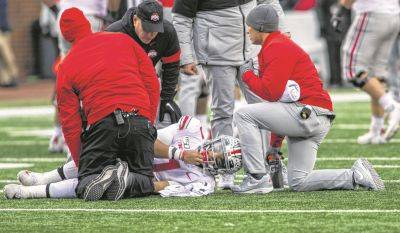 Ohio State quarterback Justin Fields gets assistance from team trainers on the field after reaggravating a knee injury during Saturday's game against Michigan in Ann Arbor, Mich. Fields returned to the game, and Ohio State won 56-27.