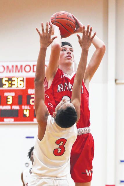 Wapakoneta's Trey Ware takes a shot against Perry's Jeffrey Simpson during the game at the Perry High School on Saturday afternoon.