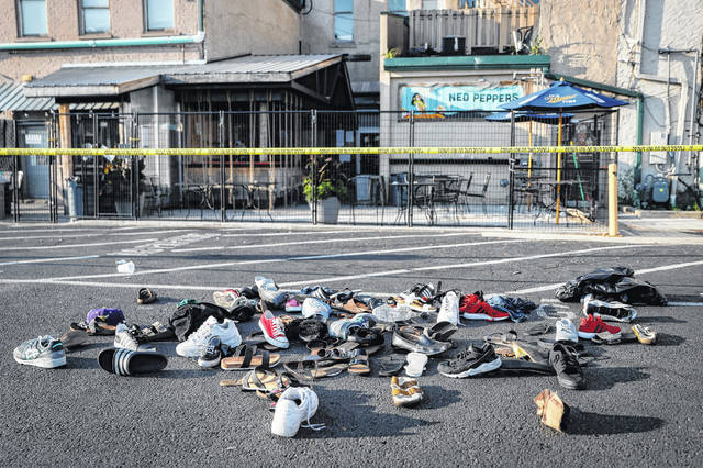Shoes are piled outside the scene of a mass shooting in Dayton, Ohio, on Sunday, Aug. 4. In a period of around 10 weeks in 2019, Dayton dealt with a Ku Klux Klan rally, a string of devastating tornadoes, and a mass shooting that killed nine people. (AP Photo/John Minchillo, File)