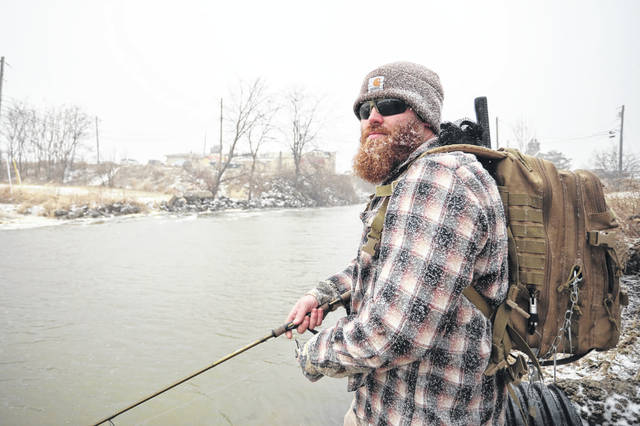 Tanner Laemmle of Van Wert braves the snow and wind while fishing at Beaver Creek in Celina on Tuesday afternoon. Amanda Wilson -The Lima News