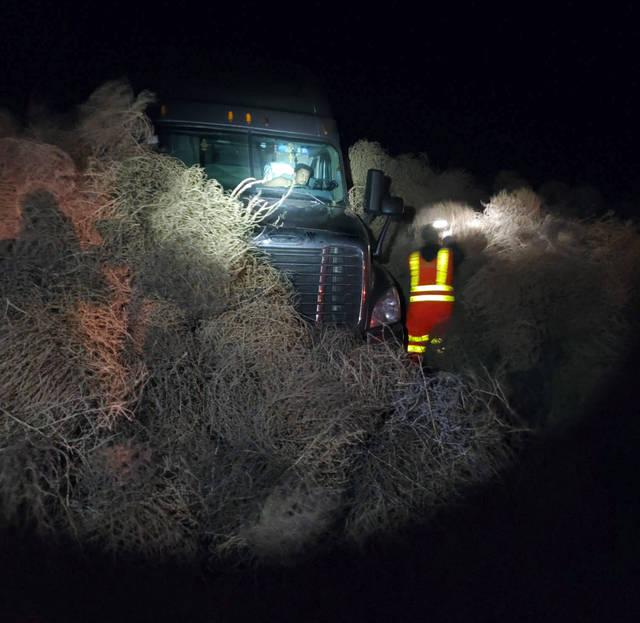 In this image taken Tuesday evening, Dec. 31, 2019, and provided by the Washington State Patrol, a vehicle is trapped by a pile of tumbleweeds along State Route 240 near Richland, Wash. (Trooper Chris Thorson/Washington State Patrol viaAP)