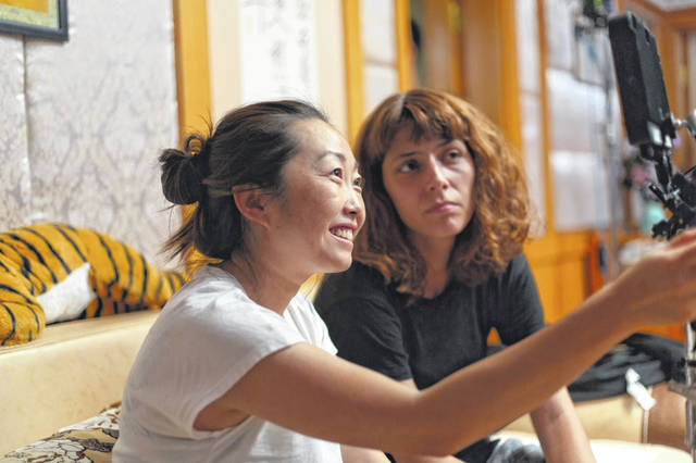 """This image released by A24 shows director Lulu Wang, left, on the set of """"The Farewell."""" Women directed 12 of 2019's top 100-grossing films in 2019, according to a study released Thursday by USC Annenberg Inclusion Initiative Female filmmakers."""