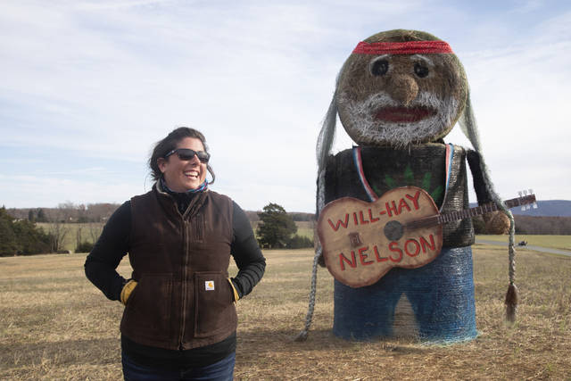 In this Tuesday, Dec. 3, 2019 photo, Huddleston native Beth Bays and artist of the hay bale sculpture Will-Hay Nelson poses for a portrait with her creation off of Tolers Ferry Road in Huddleston, Va. (Emily Elconin/The News & Advance via AP)