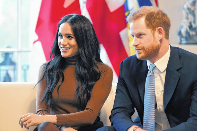 "Britain's Prince Harry and Meghan, Duchess of Sussex, smile during their visit to Canada House, in London, on Tuesday. The couple plan on ""stepping back"" as senior UK royals and work to become financially independent, they announced Wednesday."