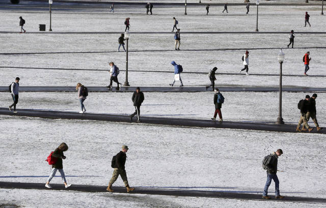 Virginia Tech students walk across the drillfield in the snow in December in Blacksburg, Va. Income-driven repayment plans help more than 8 million federal student loan borrowers afford their monthly payments. But these borrowers can still run into trouble if they don't update, or recertify, their income information on time annually.