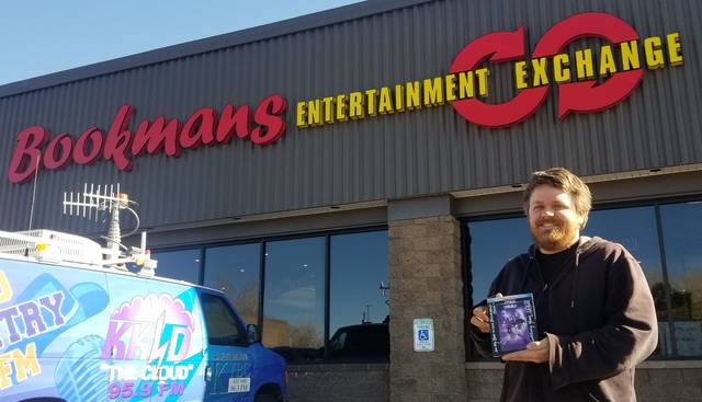"In this photo taken in Jan. 11, 2020, Bookmans Entertainment Exchange general manager Micheil Salmons stands in front of the store in Flagstaff, Ariz., holding a DVD autographed by Star Wars actor Mark Hamill. Workers at Bookmans returned to Hamill a ""Star Wars: A New Hope"" soundtrack that had been a gift from film composer John Williams. (Scott Buffon/Arizona Daily Sun via AP)"