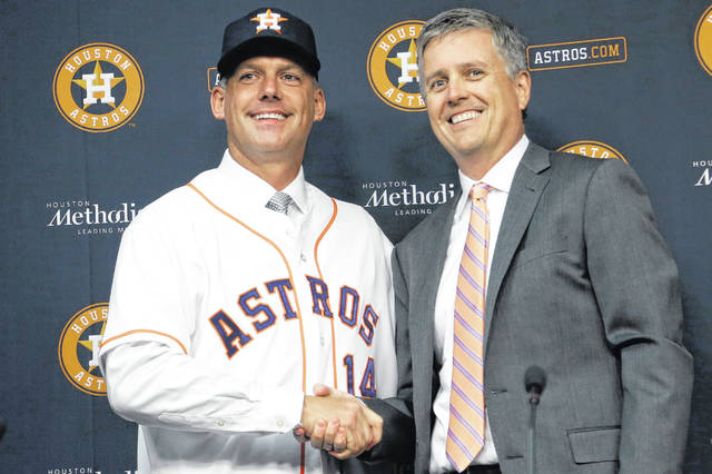 In this Sept. 29, 2014, file photo, Houston Astros general manager Jeff Luhnow, right, and A.J. Hinch pose after Hinch is introduced as the new manager of the baseball club in Houston. Hinch and Luhnow were fired Monday after being suspended for their roles in the team's extensive sign-stealing scheme from 2017.