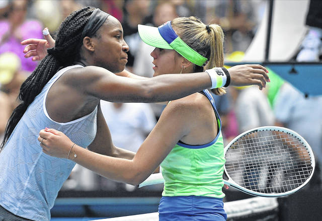 Sofia Kenin, right, of the U.S. is embraced by compatriot Coco Gauff after winning their fourth round singles match at the Australian Open tennis championship in Melbourne, Australia, Sunday, Jan. 26, 2020. (AP Photo/Andy Brownbill)