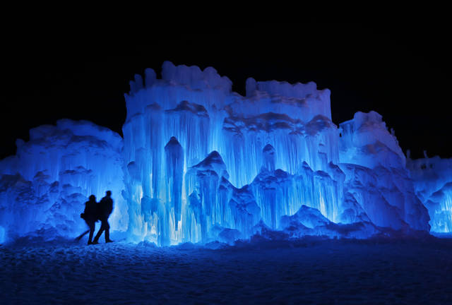 FILE – In this Saturday, Jan. 26, 2019 file photo, a couple heads toward an entrance to a cavern at Ice Castles in North Woodstock, N.H. A neighbor to the seasonal atraction alleges that melt water from the Ice Castles' property flooded her basement with over 15,000 gallons of water in April 2019. (AP Photo/Robert F. Bukaty, File)
