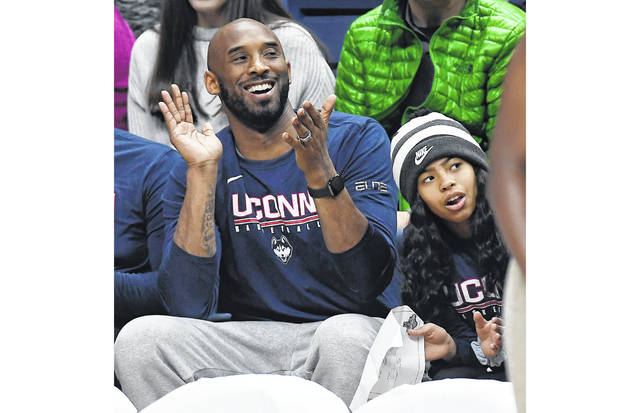 Kobe Bryant and his daughter, Gianna, watch the first half of an NCAA college basketball game March 2 between Connecticut and Houston in Storrs, Conn. Dads with daughters inspired by Kobe Bryant's special bond with his daughter took to social media to celebrate their own daughters in words and photos using the hashtag #GirlDads. Bryant and his daughter died in a helicopter crash on Sunday.