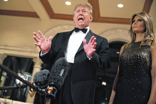 First lady Melania Trump listens as President Donald Trump speaks to reporters before his New Year's Eve party at his Mar-a-Lago property, Tuesday, Dec. 31, 2019, in Palm Beach, Fla.