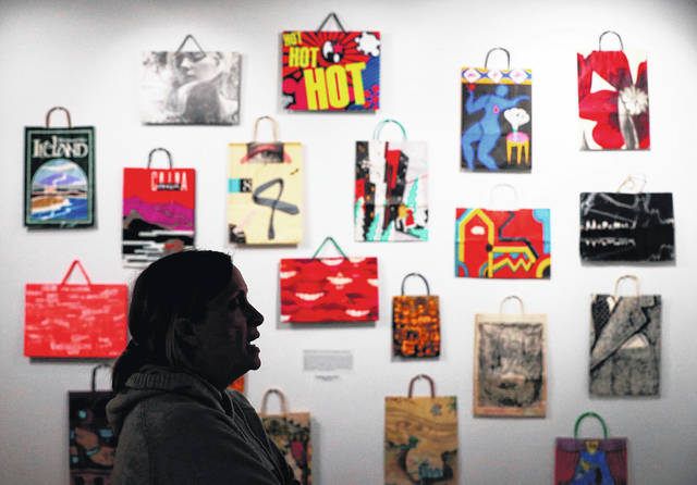 In this Tuesday, Dec. 17, 2019, photo, Jodi Kearns, director at the Institute for Human Science and Culture, takes a look at the small display of Bloomingdale's shopping bags from the Lee L. Forman Collection of Bags, in Akron, Ohio. The big batch of bags donated to UA includes shopping bags autographed by artists Andy Warhol and Roy Lichtenstein, and at least one bag from every presidential election since 1948.