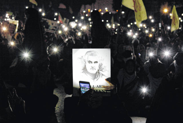 "A Shiite Muslim illuminates a portrait of Iranian Revolutionary Guard Gen. Qassem Soleimani, with light from a mobile phone, during a rally to condemn his killing in Iraq by a U.S. airstrike, in Karachi, Pakistan, Sunday, Jan. 5, 2020. Iran has vowed ""harsh retaliation"" for the U.S. airstrike near Baghdad's airport that killed Tehran's top general and the architect of its interventions across the Middle East, as tensions soared in the wake of the targeted killing."