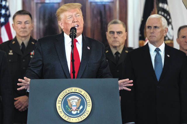 President Donald Trump addresses the nation from the White House on the ballistic missile strike that Iran launched against Iraqi air bases housing U.S. troops, Wednesday, Jan. 8, 2020, in Washington, as Chairman of the Joint Chiefs of Staff Gen. Mark Milley, Vice President Mike Pence, and others look on.