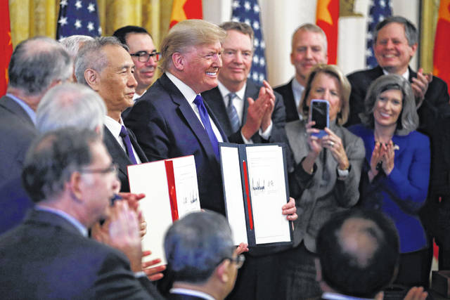 President Donald Trump, center, and Chinese Vice Premier Liu He, left, hold the U.S. China Trade Agreement after signing it in the East Room of the White House, Wednesday, Jan. 15, 2020, in Washington.