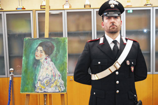"""An Italian Carabiniere, paramilitary police officer, stands near a painting which was found last December near an art gallery and believed to be the missing Gustav Klimt's painting 'Portrait of a Lady' during a press conference in Piacenza, Italy, Friday, Jan. 17, 2020. Art experts have confirmed that a stolen painting discovered hidden inside an Italian art gallery's walls is Gustav Klimt's """"Portrait of a Lady,"""" Italian prosecutors said Friday. A gardener reported finding an art work inside a bag last month while clearing ivy at the Ricci Oddi Modern Art Gallery in the northern city of Piacenza. """"Portrait of a Lady"""" disappeared from the gallery during renovation work in February 1997."""